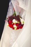 Bride holding wedding bouquet of red and white roses Royalty Free Stock Image