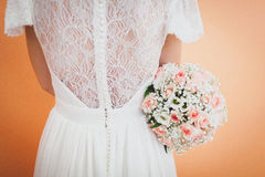 Bride holding a wedding bouquet. And turning back to the camera Stock Photo