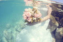 Bride holding wedding bouquet underwater Stock Photography