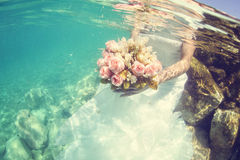 Bride holding wedding bouquet underwater Royalty Free Stock Photography