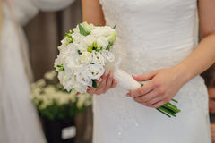 Bride holding wedding bouquet of white flowers.  Royalty Free Stock Images