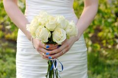 Bride holding wedding bouquet of white  roses Stock Photo