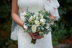 Bride holding a wedding bouquet of white roses.  Stock Images