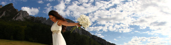 Bride holding white bouquet in nature. Panorama of young beautiful woman in long white dress holding bouquet with mountains in background Royalty Free Stock Photography