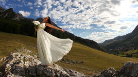Bride holding white bouquet in nature. Young beautiful woman in long white dress in the wind holding bouquet with mountains in background Royalty Free Stock Image