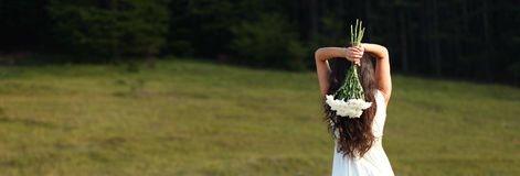 Bride holding white bouquet over head in nature. Scenic panoramic view of young beautiful woman in white dress holding bouquet above head near forest Royalty Free Stock Images