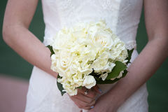 Bride Holding White Bouquet of Roses. Zoomed in to bride`s mid-section to show flower detail Stock Image