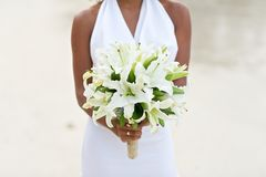 Bride holding white lily flower wedding bouquet. On white sand beach Royalty Free Stock Image