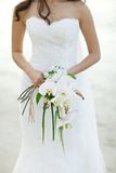 Bride holding white orchid flower wedding bouquet. With beach background Stock Photography