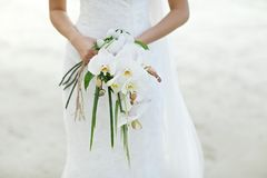 Bride holding white orchid flower wedding bouquet. With beach background Stock Image