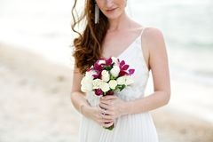 Bride holding white rose flower wedding bouquet. Bride holding white rose and purple orchid flower wedding bouquet on beach with sea background Stock Photography