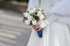 Bride holding white wedding bouquet Stock Images