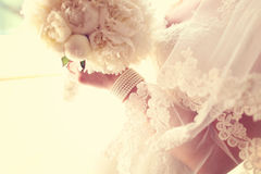 Bride holding white wedding bouquet. Hands of a bride holding white peonies bouquet Royalty Free Stock Photo