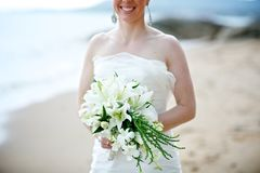 Bride holding white wedding bouquet. Bride holding white lily flower wedding bouquet on beach withe sea in background Stock Photography