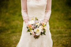 Bride holding white wedding bouquet. Bride holding wedding bouquet with Peonies, Tulips, Parrot Tulips, Roses, Dusty Miller, and Astilbe Royalty Free Stock Photography