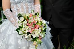 Bride holding white wedding bouquet of roses Royalty Free Stock Images