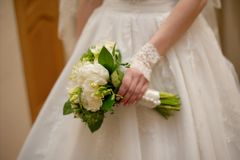 Bride holding white wedding bouquet of roses and love flower Stock Photo