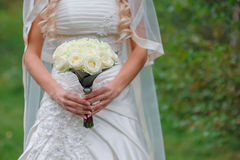 Bride holding white wedding bouquet of roses and love flower.  Stock Photography