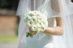 Bride holding white wedding flowers bouquet Stock Images