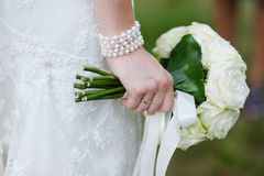 Bride holding white wedding flowers bouquet. Bride holding beautiful white wedding flowers bouquet Royalty Free Stock Photos