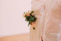 Bride holds a beautiful bouquet from orange and white flowers standing near groom Royalty Free Stock Photos