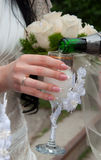 Bride holds a beautiful glass with champagne. The hand of the bride with manicure  holds a beautiful glass with champagne Royalty Free Stock Photography