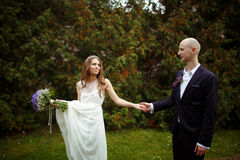 Bride holds a bouquet and a dress in one arm and groom's hand in Royalty Free Stock Image