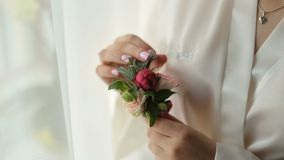 Bride holds boutonniere in her hands on wedding preparation stock video