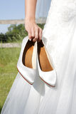 Bride holds bridal shoes in hand Royalty Free Stock Image