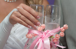 Bride holds a glass with champagne. The hand of the bride with manicure  holds a glass with champagne Royalty Free Stock Photos