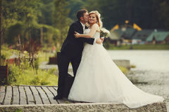Bride holds groom's hand while he hugs her on the lake's shore Royalty Free Stock Images