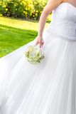 Bride holds in hand a wedding bouquet of flowers in a garden Royalty Free Stock Photos