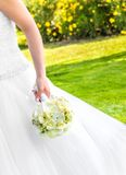 Bride holds in hand a wedding bouquet of flowers in a garden Stock Photography