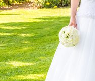 Bride holds in hand a wedding bouquet of flowers in a garden Royalty Free Stock Photography