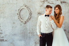 Bride holds her hands on groom& x27;s shoulders stock image