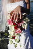 Bride holds her ring over bouquet Royalty Free Stock Photography