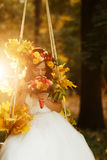 Bride holds a red wedding bouqet in her arms sitting on the swing illuminated with autumn sun.  royalty free stock images