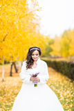 Bride holds wedding bouquet of flowers in autumn park Royalty Free Stock Photo