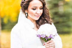 Bride holds wedding bouquet of flowers in autumn park Stock Photo