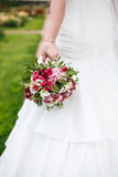 Bride holds wedding bouquet of flowers Stock Images