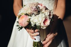 The bride holds a wedding bouquet of peonies in her hands stock photography