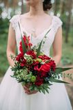 Bride holds wedding bouquet with red flowers. Bride holds wedding bouquet with burgundy flowers and greens, her face is invisible Royalty Free Stock Photos