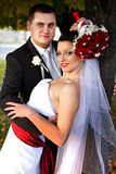 Bride holds a wedding bouquet under a head while groom hugs her Stock Images