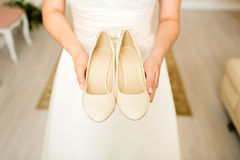 Bride holds wedding shoes in hands stock photo