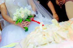 The bride holds a white rose bouquet in her hand. Bouquet of flowers of the bride. The bride holds a wedding bouquet of flowers in Royalty Free Stock Image