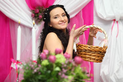 Bride holds wicker basket and looks at camera Stock Photos