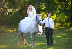 Bride on a horse beside her husband in the forest Stock Images
