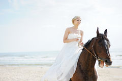 Bride on a horse by the sea Royalty Free Stock Image