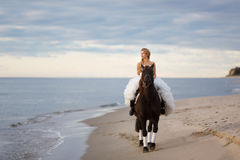 Bride on a horse by the sea Royalty Free Stock Photo