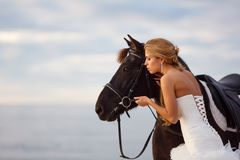 Bride with a horse by the sea Stock Photography